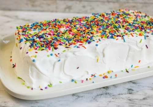 white frosted cake with sprinkles